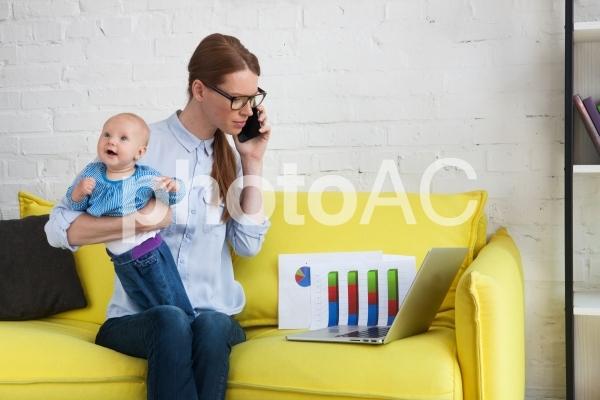 自宅で赤ちゃんを抱っこしながら仕事するお母さん10の写真