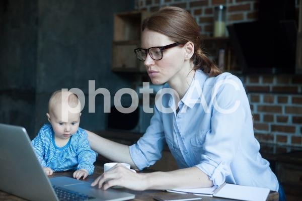 自宅で赤ちゃんの世話をしながら仕事するお母さん2の写真