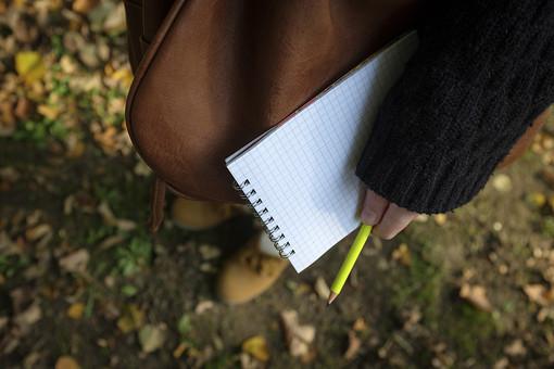 女性 レディ おんな 女子 学生 記者 ライター ペン 鉛筆 黄色 ノート 手帳 メモ帳 マス目 方眼紙 リング 文具 かばん バッグ 取材 記録 観察 考察 スケッチ 筆記 開く 持つ 携える 立つ 左手 公園 学校 キャンパス 落ち葉 屋外 野外 日光