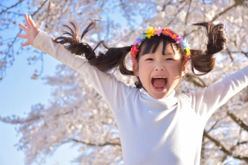 桜の下でジャンプする子供の写真