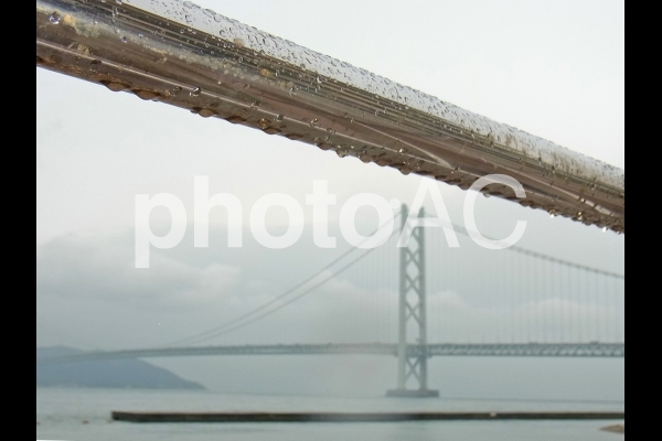 フェンスに伝う雨つぶと明石海峡大橋の写真