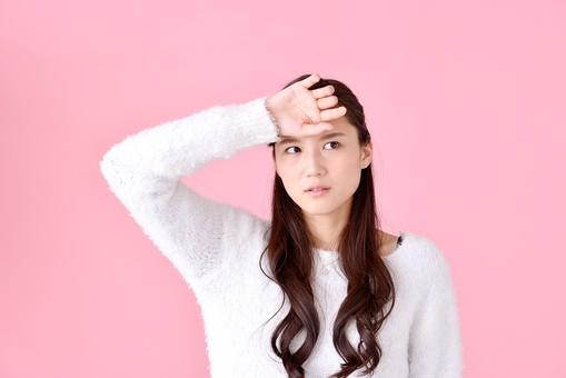 人物 女性 日本人 若者 若い  20代 美人 かわいい ロングヘア カジュアル  ラフ 私服 セーター ニット 屋内  スタジオ撮影 背景 ピンク ピンクバック ポーズ  おすすめ 上半身 額 頭 押さえる 発熱 熱 風邪 病気 暑い 頭痛 mdjf007