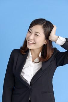 人物 女性 日本人 20代 若者  ビジネス スーツ 黒 紺色 セミロング  OL 社会人 会社員 ビジネスマン 就活  就職活動 真面目 ポーズ 屋内 スタジオ撮影  ブルーバック 上半身 頭をかく 照れる 恥ずかしい 照れ笑い 失敗 笑顔 mdjf013