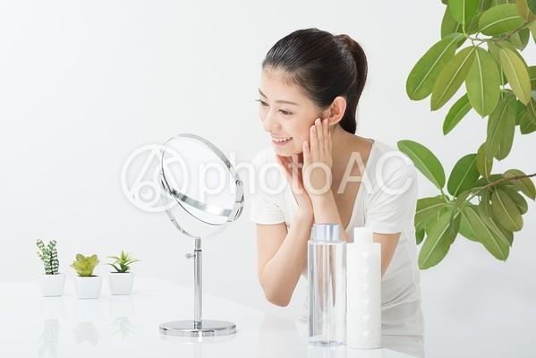 鏡で肌をチェックする女性(正面)6の写真