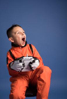 背景 ダーク ネイビー 紺 男の子 男子 男児 男 子ども こども 子供 1人 ひとり 一人 児童 宇宙服 宇宙 服 スペース スペースシャトル 宇宙飛行士 飛行士 オレンジ 希望 夢 将来 未来 体験 職業体験 職業 小道具 小物 おもちゃ コントローラー リモコン コントロール 座る 腰かける 驚く びっくり ビックリ 衝撃 焦る  外国人 mdmk009