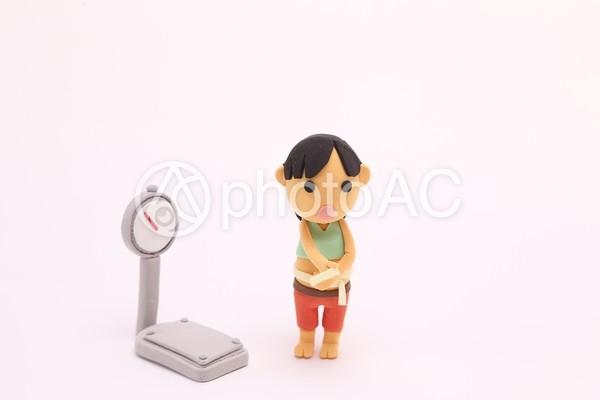 粘土人形 お腹を測る人1の写真