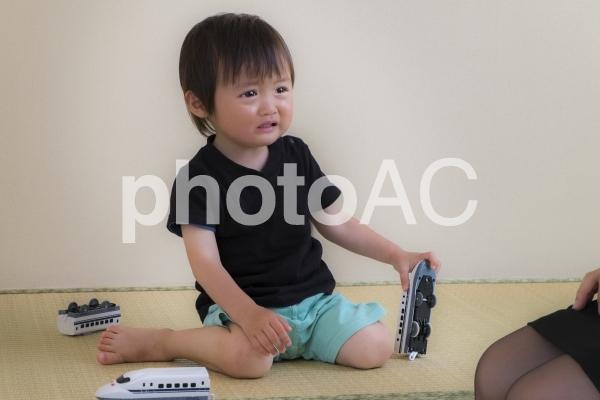 畳の間で泣く2歳児の写真