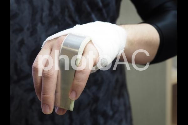 骨折 包帯 副木 指 固定  男性の写真
