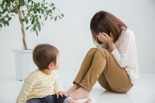 遊ぶ赤ちゃんと泣く女性の写真
