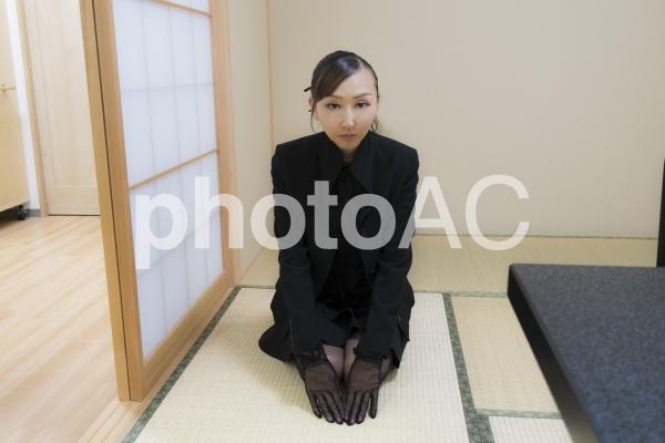 訃報を聞いて喪服で駆けつける女性の写真