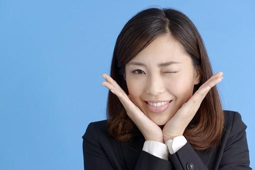 人物 女性 日本人 20代 若者  ビジネス スーツ 黒 紺色 セミロング  OL 社会人 会社員 ビジネスマン 就活  就職活動 真面目 ポーズ 屋内 スタジオ撮影  ブルーバック 上半身 正面 表情 舌を出す 失敗 うっかり ちゃっかり あっかんべー 両手 頬 手を当てる ウインク 笑顔 mdjf013