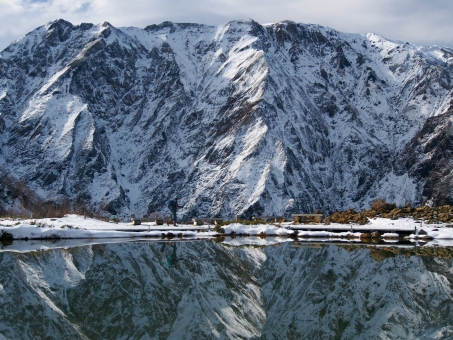 水鏡のような池のほとりを歩く人【北アルプス八方池】の写真