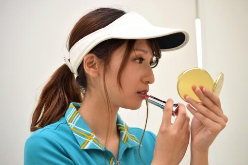メイク直しをするゴルフ女子の写真