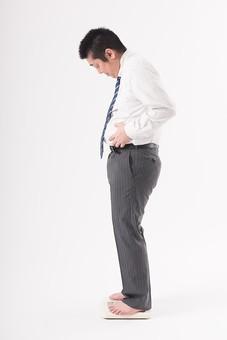 日本人  男性 一名 一人 1人 ぽっちゃり 肥満 ダイエット 痩せる 痩せたい 目標 ビフォー アフター 太っている 太り気味 メタボ メタボリックシンドローム 脂肪 体系 ボディー 白バック 白背景 スーツ サラリーマン 営業マン ネクタイ ビジネスマン 仕事 体重計 横向き お腹を触る 気になる 気にする 体重計に乗る 体重を計る mdjm017