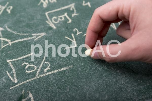 黒板とチョークと手の写真