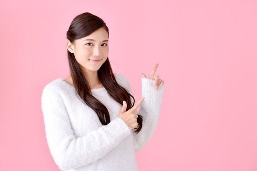 人物 女性 日本人 若者 若い  20代 美人 かわいい ロングヘア カジュアル  ラフ 私服 セーター ニット 屋内  スタジオ撮影 背景 ピンク ピンクバック ポーズ  おすすめ 指差し 指さす 両手 上 注目 案内 ポイント 説明 アドバイス 笑顔 上半身 mdjf007