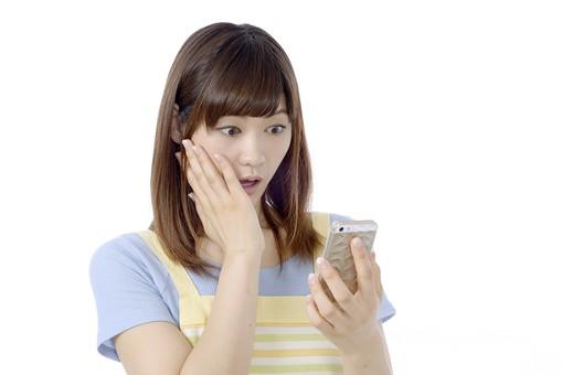 人物 屋内 白バック 白背景 日本人 1人 女性 20代 30代 エプロン  奥さん 奥様 婦人 家庭人 夫人 主婦 若い ポーズ 表情 驚く 驚いた びっくり  携帯電話 携帯 電話 スマホ スマートフォン 画面 見る 下を向く うつむく 指 手 持つ mdjf018