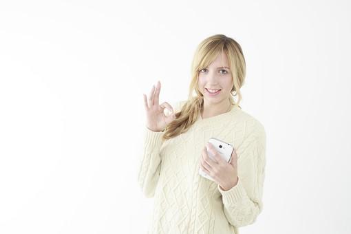 人物 女性 20代 外国人 外人  外国人女性 外人女性 モデル 若い セーター  ニット 私服 カジュアル ポーズ 金髪  ロングヘア 屋内 白バック 白背景 OK サイン 合図 ジェスチャー 大丈夫 許可 良い スマホ スマートフォン 上半身 笑顔 ハンドサイン mdff045