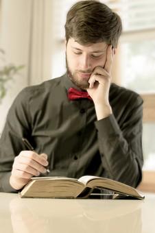 本 ブック 書物 書籍 図書 読書 読む 趣味 勉強 人物 男性 男 外国人 若い 若者 髭 20代 上半身 頬杖 ペン 書く 考える 考え込む 俯く ページ 捲る めくる 開く 接写 クローズアップ mdfm079