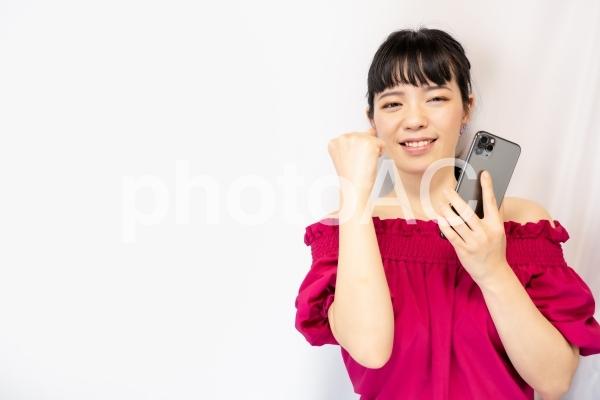 スマホを持ってガッツポーズをする女性(白背景)の写真