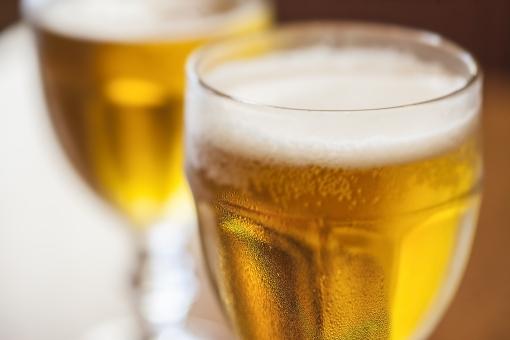 飲み物 ビール お酒 琥珀色 グラス グラスビール 乾杯 よく冷えている 背景素材 ポストカード 待ち受け画像 コピースペース 冷たいビール テクスチャー デザイン素材 光透過光 おいしそう 仕事の後 休日 日曜日 ビアグラス シズル感 水滴