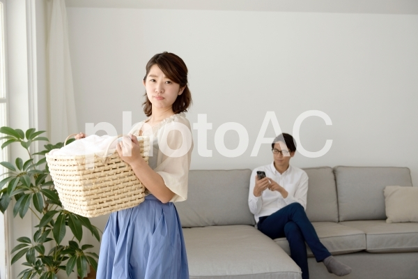 洗濯物のかごを持つ母とスマホを操作中の父1の写真