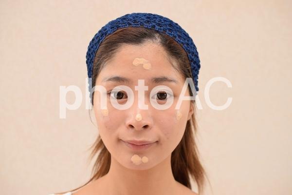 化粧下地/ファンデーションを顔に乗せる女性の写真