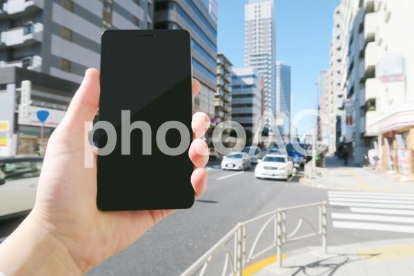 歩きスマホをする男性の手と街並みの写真