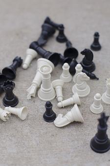 チェス 駒 マス キング クイーン ルーク ビショップ ナイト ポーン 黒 白 ブラック ホワイト 先手 後手 チェスピース ピース ゲーム ボードゲーム マインドゲーム ルール 知能 考える 予想 予測 技能 戦略 勝者 敗者 勝利 敗北 地面 倒れた 散らばった