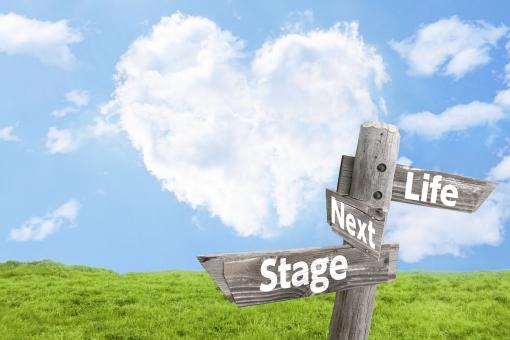 ハート雲と草原とライフステージを示す道しるべの写真