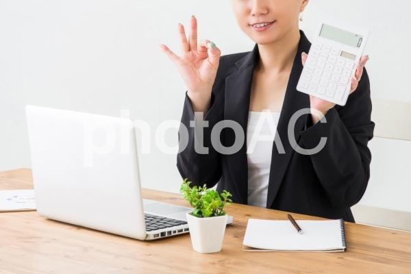電卓を持って説明する女性の写真
