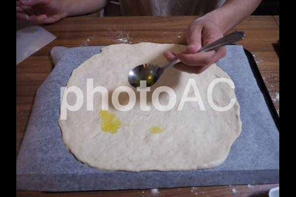 自宅で焼くピザ生地にオリーブオイルを塗っているところの写真