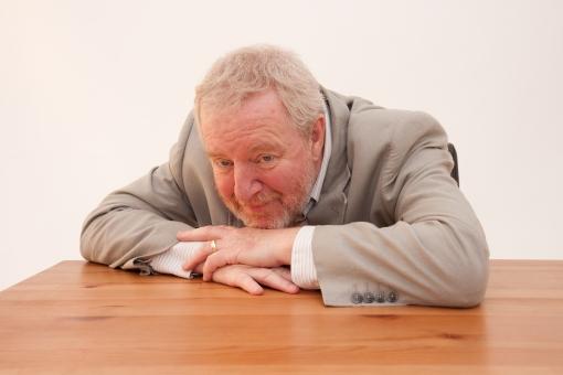 シニア 外国人 正面 ひげ 髭 上半身 髭面 白髪 ジャケット 白背景 グレー シャツ 一人 初老 疲労感 疲れ 倦怠感 うつぶせ 俯伏せ 両手 顎 付ける テーブル 木目 やれやれ 斜め左視線 室内 男性 mdjms002