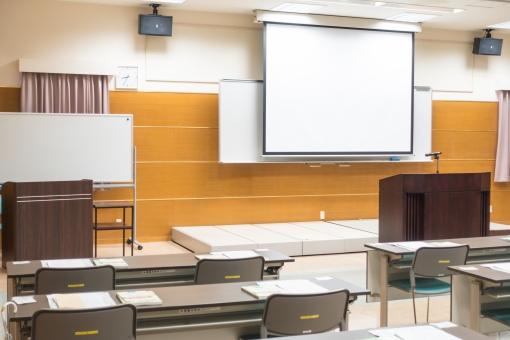 講習会 セミナー 壇上 室内 テーブル 参考書 講師 先生 講義 研修 授業 資格 コンサルタント スキル 知識 イス マイク スクリーン モニター 受講者 ビジネス 企画 照明 会場 カーテン 能力