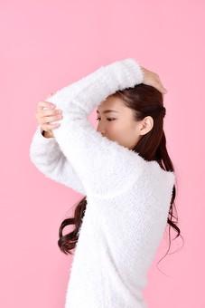 人物 女性 日本人 若者 若い  20代 美人 かわいい ロングヘア カジュアル  ラフ 私服 セーター ニット 屋内  スタジオ撮影 背景 ピンク ピンクバック ポーズ  おすすめ 上半身 横向き 横顔 肘 伸ばす ストレッチ mdjf007