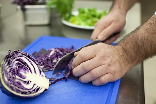 厨房 台所 キッチン 料理 調理  コック シェフ 料理人 包丁 ナイフ 切る カット まな板 レストラン 仕込み 下準備 野菜 青 バット ボディパーツ 腕 持つ 手 紫キャベツ レッドキャベツ 赤きゃべつ  千切り やり方 切り方 細かい 細かく  男性 外国人