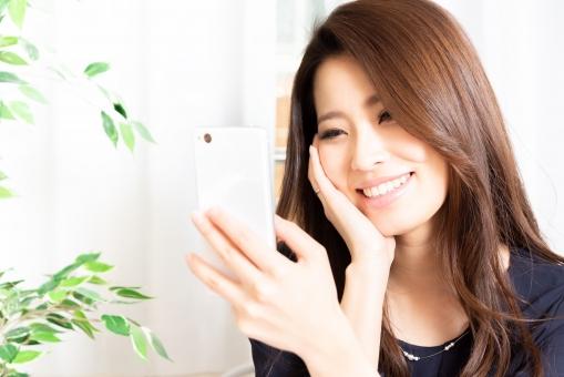 スマホを見る笑顔の女性の写真