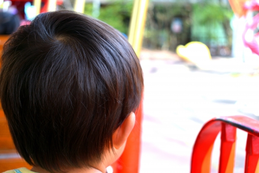 遊園地のアトラクションに乗る楽しそうな幼児の写真