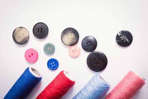 ソーイング 縫い物 裁縫 洋裁 手芸  手仕事 裁縫道具 裁縫用品 アップ 素材  趣味 ハンドメイド ホビー 生活 暮らし  小物 手縫い ファッション 縫う 針仕事 ボタン ボタンつけ 糸 糸巻き 複数 白バック 白背景 散らばる