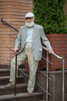 病院 医院 診療所 屋外 外 玄関 エントランス 階段 入口 外国人 白人 男性 老人 高齢 高齢者 おじいさん おじいちゃん 髭 ヒゲ ひげ 白髪 ハンチング帽 上着 ジャケット 立つ 下りる 手すり 杖 つえ サングラス 全身 もたれる ポーズ mdjms016