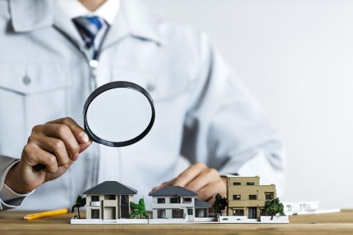 住宅模型をルーペで覗く作業服の男性の写真