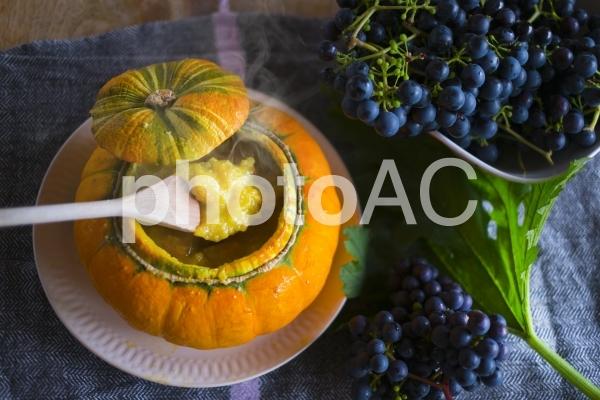 かぼちゃの器のかぼちゃスープとぶどうの写真