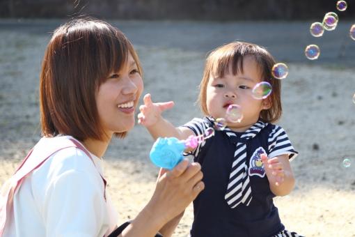 シャボン玉で遊ぶ女性と子供2の写真