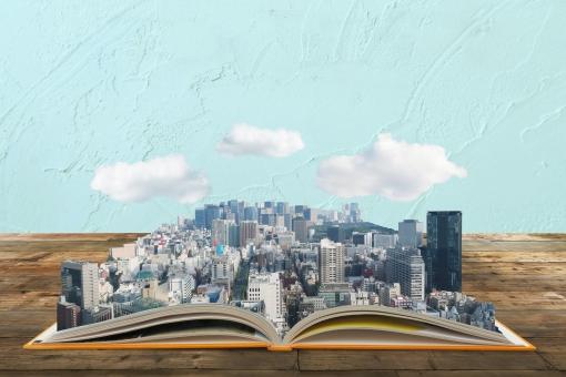 都市計画のシミュレーションと書籍-木目の机と青い壁の写真