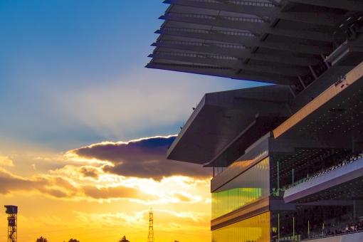夕日 夕焼け 夕方 西日 空 青空 燃える オレンジ 黄色 競馬場 スタンド ガラス 反射 観客席 応援席 屋根 太陽 光