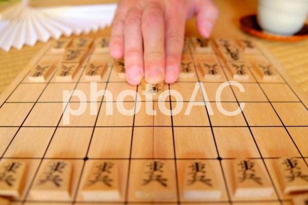 将棋の駒を進める男性の手の写真