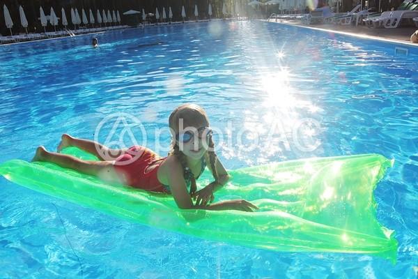 プールでフロートマットで浮かんでいる女の子3の写真
