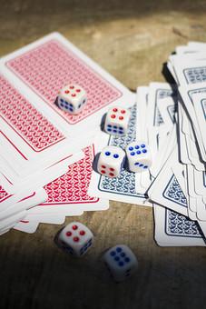 トランプ カード ゲーム 札 娯楽 木 屋外 茶色 机 テーブル 赤 青 裏側 裏 絵札 黒 木目 手品 マジック 遊び 絵札 乱雑 サイコロ  重ねる 配る 切る カードゲーム