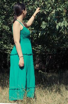 外国 海外 屋外 野外 自然 人物 1人 外国人 白人 セルビア人 大人 若い 女性 女 女の子 横向き 後頭部 ブルネット 黒髪 セミロング まとめ髪 ひっつめ髪 無造作ヘア 普段着 青緑の服 ワンピース ロングワンピース ノースリーブ キャミソールワンピース ネックレス ペンダント レザーコード ブレスレット 指輪 リング アクセサリー 眼鏡 メガネ めがね 低木 木 果樹 木の実 果実 木立 芝生 mdff021