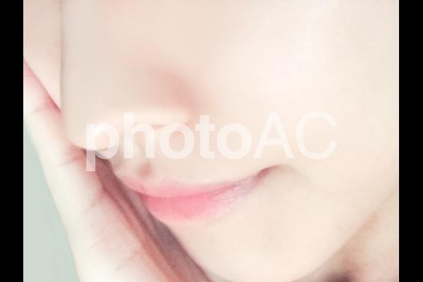 頰に手を当てる女性の写真